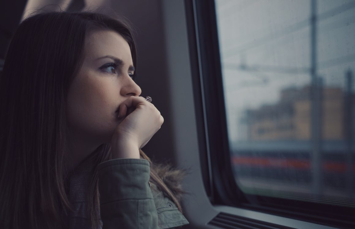 girl staring into the distance on a train